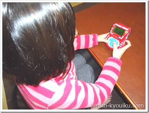 進研ゼミ小学講座チャレンジ2年生のふろく「九九・漢字バトルマシーンDX(デラックス)」で楽しく勉強中の女の子